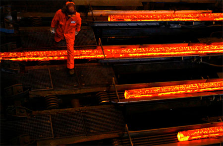 A worker walks over hot steel plates at the factory of Swiss Steel AG. REUTERS/Michael Buholzer