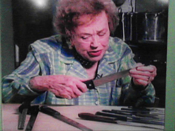 old julia child looking at stainless steel knives