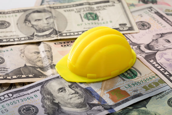 hard hat sitting on US banknotes
